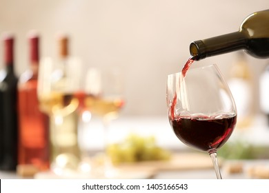 Pouring red wine from bottle into glass on blurred background. Space for text