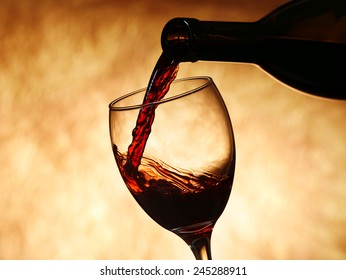 Pouring red wine from bottle into glass on color background