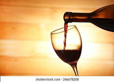 Pouring red wine from bottle into glass on wooden planks background