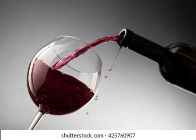 Pouring red wine from bottle into the wineglass
