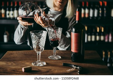 Pouring red wine from decanter onto glasses