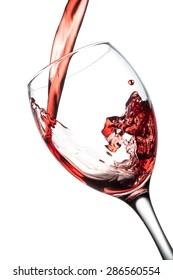 Pouring red wine in a wine glass, isolated on a white background