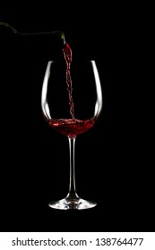 Pouring a red wine glass on black background