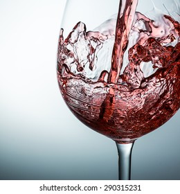 Pouring red wine in a glass on gray background