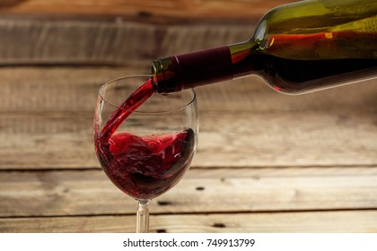 Pouring red wine in a glass on a wooden table