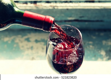 pouring red wine. Wine in a glass. selective focus, motion blur, Red wine in a glass. Sommelier wine into the glass on a blue background old.