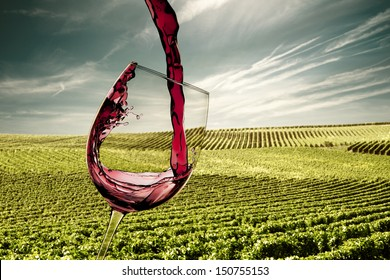 pouring red wine glass with vines landscape
