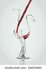 Pouring red wine to glass with water splashes on white background