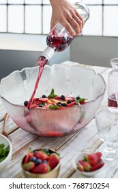 Pouring red wine into bowl filled with sliced fruit strawberries blueberries and fresh herbs, preparing sangria party punch
