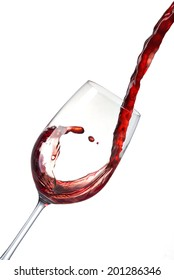 Pouring red wine into a crystal glass and creates waves, splash. Red wine poured from bottle into a glass isolated on white background