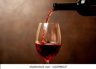 Pouring red wine into a glass, close-up