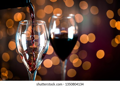 Pouring red wine into the glass. Golden bokeh background.