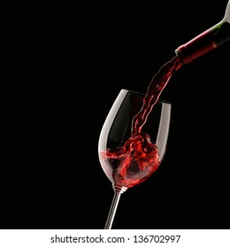 Pouring red wine into wine glass on a black background