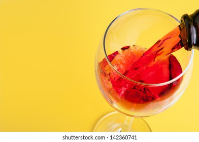 Pouring red wine into a glass on a yellow background