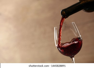 Pouring red wine into glass from bottle against blurred beige background, closeup. Space for text