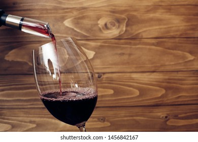 Pouring red wine into a wine glass with decanter or aerator attached to bottle neck. Rustic wooden background. Place for text. Copy-space.