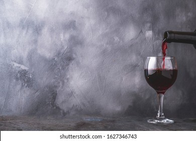 Pouring  red wine into glass on gray background. Copyspace