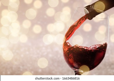 Pouring red wine into a glass from a bottle
