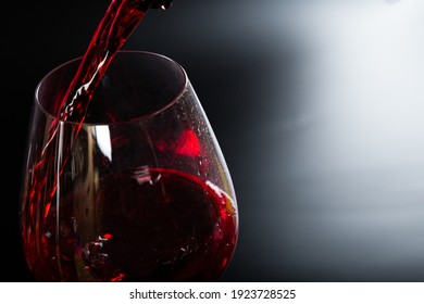 Pouring red wine into a glass on a black background. splashes and drops
