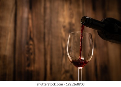 Pouring red wine into the glass against wooden blurred background.