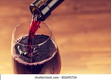 roter Wein in das Glas auf Holzhintergrund gießen