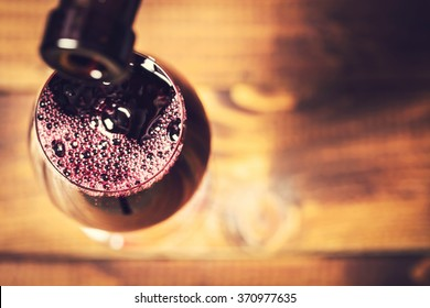 Pouring red wine into the glass against wooden background. Soft focus