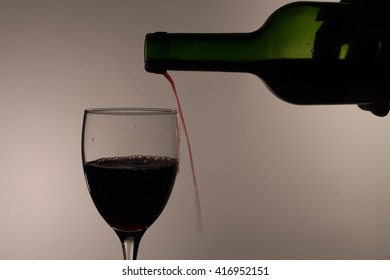pouring red wine into a glass in dim light. sheds wine by the glass