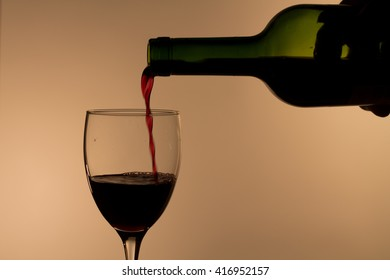 pouring red wine into a glass in dim light