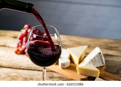 Pouring red wine into the glass against wooden table