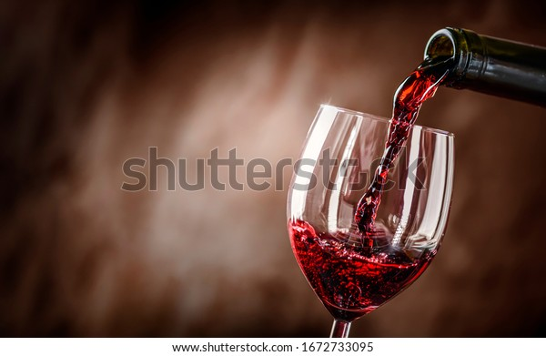 Pouring red wine into the glass against rustic background.  Pour alcohol, winery concept.