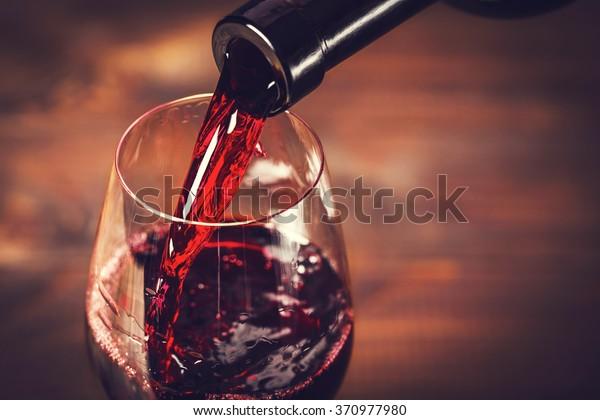 Выливание красного вина в бокал на деревянном фоне