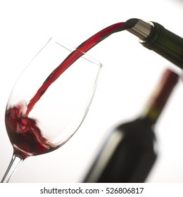 Pouring red wine into wineglass from green bottle, white background