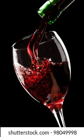 pouring red wine isolated on a black background