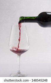 Pouring red wine on glass on a solid bright background
