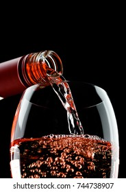 Pouring rose pink wine from bottle to glass isolated on black background