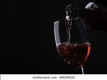 Pouring rose wine from bottle into the wineglass