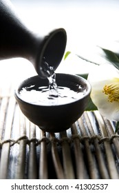 Pouring sake into Japanese traditional cup and white camellia