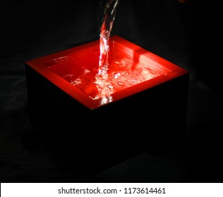 Pouring sake, Japanese traditional alcoholic drink, in a lacquered red container, masu,  on black background