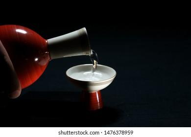 Pouring sake or Nihonshu or Japanese rice wine into a sake cup or Ochoko from a sake bot or tokkuri
