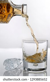 Pouring scotch from a crystal decanter into a whiskey tumbler glass on white background