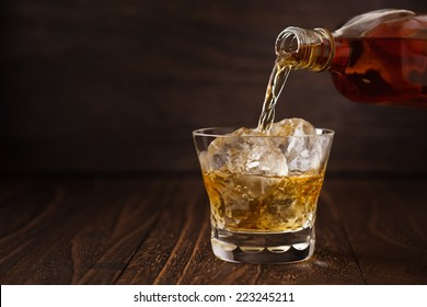 Pouring Scotch drink into glass