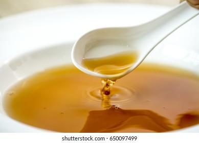 Pouring  shabu shabu soup into a bowl with a ladle on white
