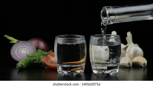 Pouring up shot of vodka from a bottle into glasses with onion, hot pepper, cherry tomato, dill and garlic against black background. Pour of alcohol drink