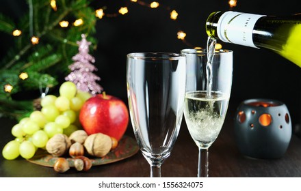Pouring sparkling white wine in glasses on Christmas table. Christmas tree, lights and decorations in the background.