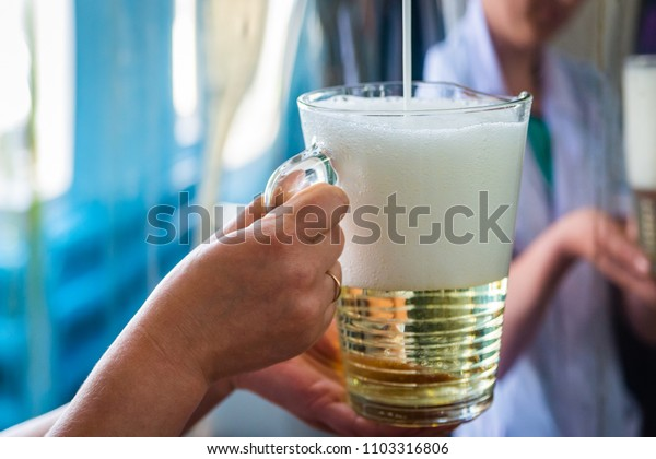 Pouring sparkling wine in glass jug at winery