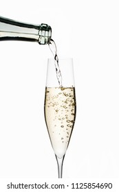 Pouring sparkling wine into glass on white background