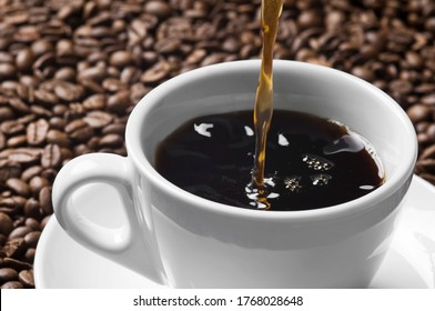 Pouring stream of hot coffee to white cup on roasted coffee beans background. Close up of a brown surface texture of aroma black caffeine drink ingredient for coffee beverage