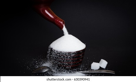 Pouring sugar into a little cup in front of black background - Concept of sugary drinks