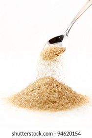 Pouring a tablespoon of brown sugar onto a pile of sugar.