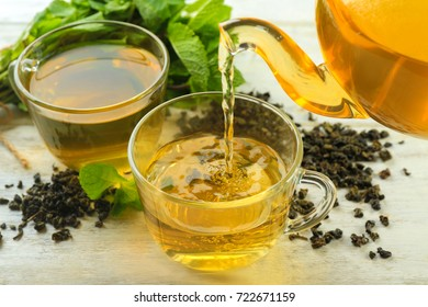 Pouring tasty mint tea into cup on table